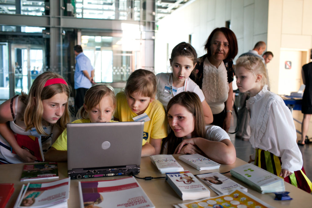 Nauczycielka i dzieci skupione wokół jednego komputera